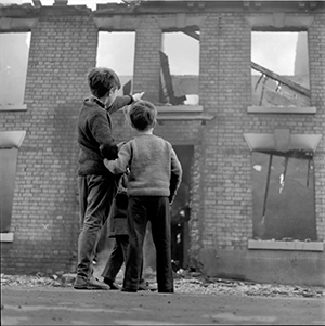 Photograph of kids in a street with burning houses, Hull.