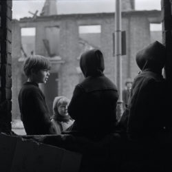 Black and white photograph of children in a demolished street in Hull.