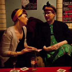 Colour photograph of two girls in a bar wearing turbans