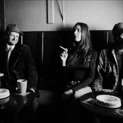 Black and white photograph of three people in a bar