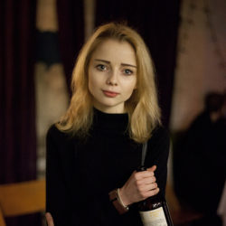 Photograph of a young girl clutching a bottle in a bar.