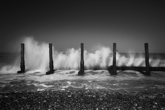 Black and white photograph of waves breaking on the Norfolk coast.