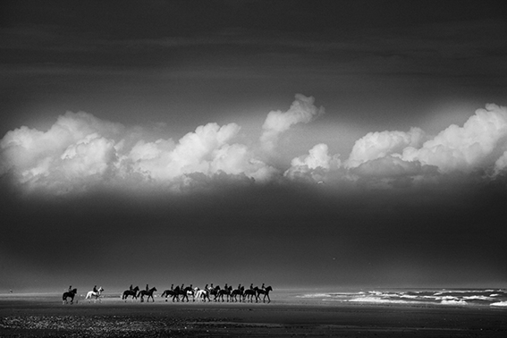 Black and white photograph of the Household Cavalry on Holkham sands.