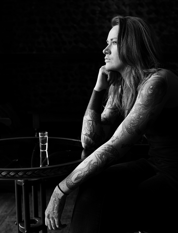 Photograph of tattooed girl in a bar.