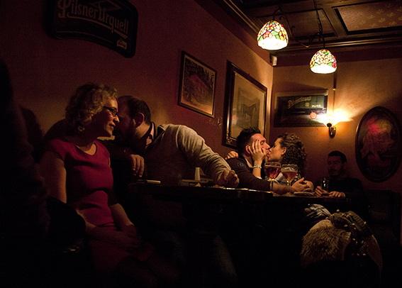 Photograph of a couple kissing in a bar.