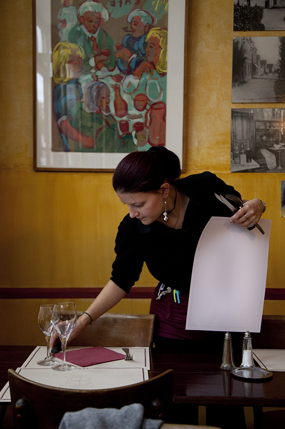 Photograph of a waitress in a bar.
