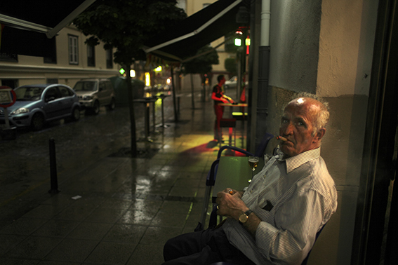A photograph of an angry older Spaniard with a glowing cigar.