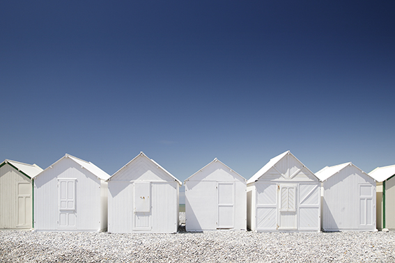 Photograph of white beach huts Normandy.
