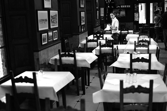 Black and white photograph of a waitress laying tables.
