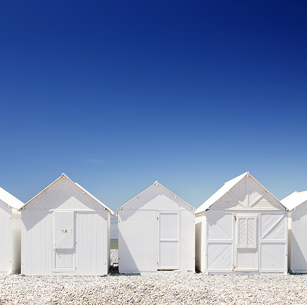 Photograph of white beach huts against a blue sky.