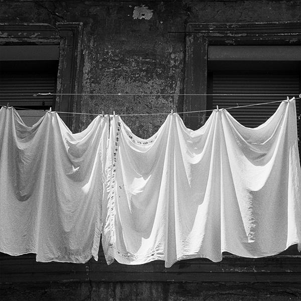 Black and white photograph of washing on a Spanish balcony.