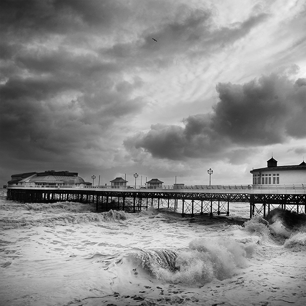 Black and white photograph of Cromer pier during a storm.