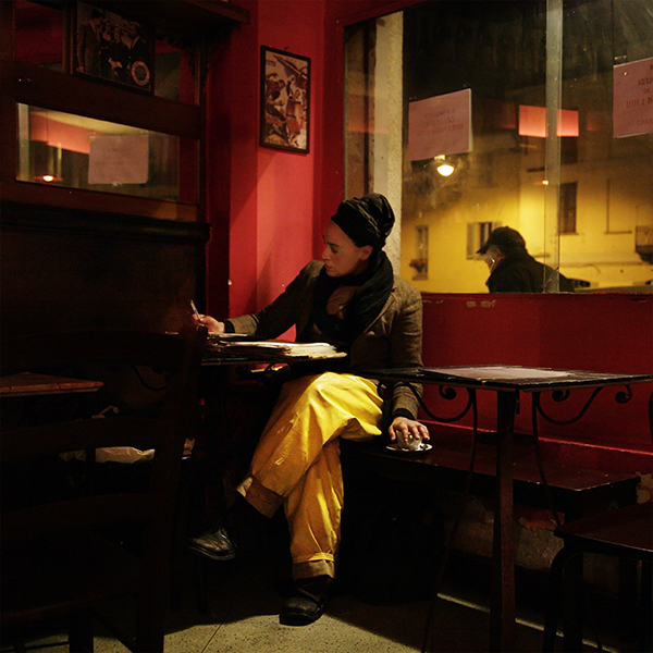 Photograph of a girl in a bar wearing yellow trousers.