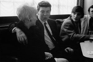 Black and white photographs of young trawler men in a pub, one of whom has his arm around his girlfriend, Hull 1971.