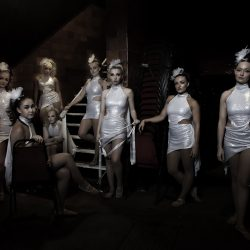 A back stage photograph of the Hippodrome dancers in white costumes.