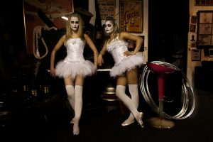 Two circus dancers in tutus with vampire make up.