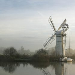 Early morning photograph of the wind pump and clearing mist at Thurne Norfolk.