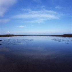 Photograph of Holkham sands filled with water, reflecting clouds.