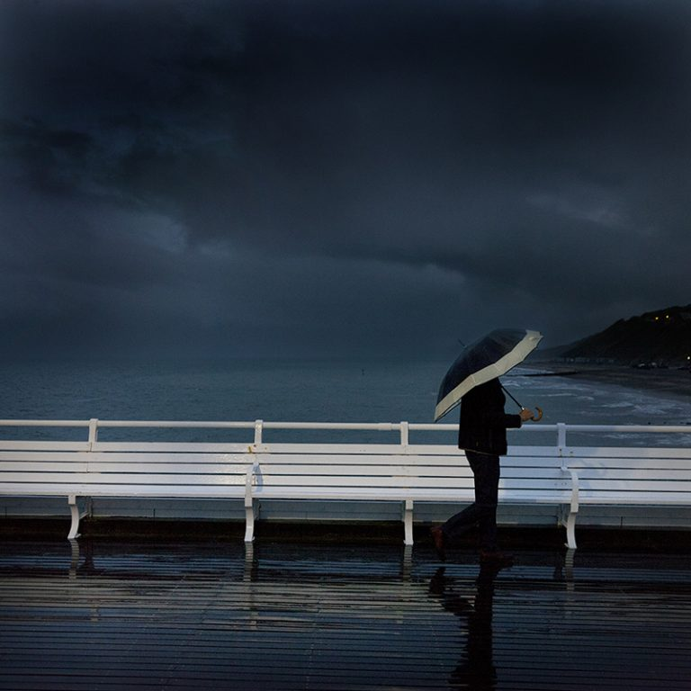 Photograph of a man with an umbrella on Cromer pier taken at dusk.