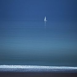 Photograph of a sailing boat going past Cromer on a calm sea.