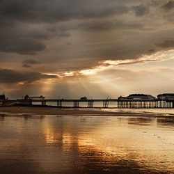 Photograph of the sun going down over Cromer pier and town.