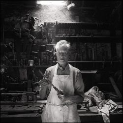 Black and white photograph of a coffin maker in his workshop.