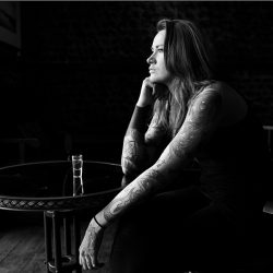 Black and white photograph of a Tattoo Artist with bare arms in a bar.