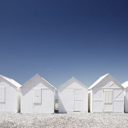 Photograph of white beach huts against a blue sky on the Normandy coast.