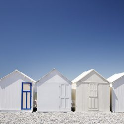 Photograph of white beach huts and one blue door in Normandy.