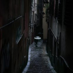 Photograph of a man with an umbrella in the rain in Genoa.