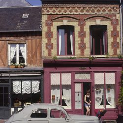 Photograph of an old French house and car in France.
