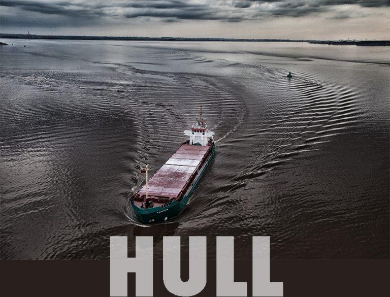 Colour photograph of a ship going under Humber bridge.