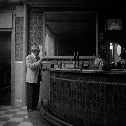 Black and white photograph of a man at the bar of the King Billy pub Hull early 1970's.
