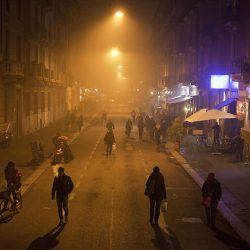 Colour photograph of people going home in the mist in Milan.