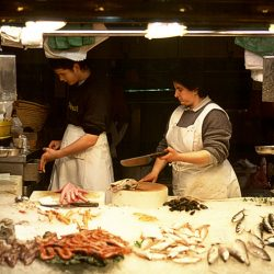 Colour photograph of a Fishwife in Barcelona Fish Market passing a knife.