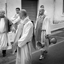 Black an white photograph of priests, one with a megaphone in Southern Italy.