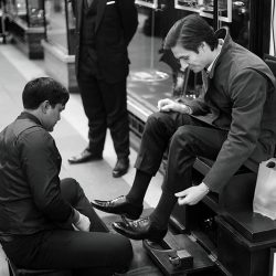 A black and white photograph of a shoeshine at work in London
