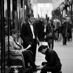black and white photograph of a shoeshine at work in London.