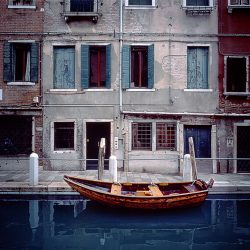 Photograph of a boat in an old part of Venice.