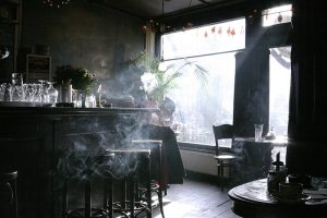 Photograph of a couple in an Amsterdam bar, the lady is smoking near a window.