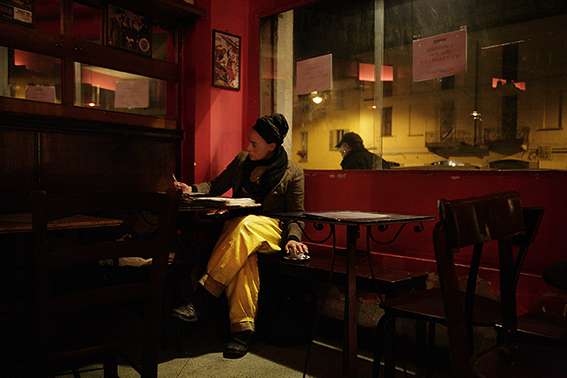 Photograph of a girl wearing yellow trousers in a bar.