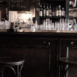 Photograph of a bar and two empty stools.