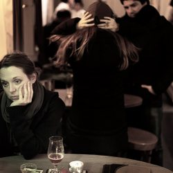 A photograph of a bored looking young women in a bar in Bruges.
