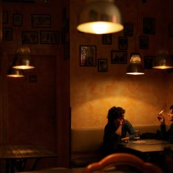 Photograph of a young couple alone having a drink in a bar in Milan.
