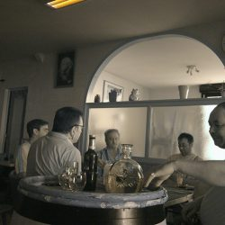 Infrared photograph of men playing cards and drinking Pernod in a bar in France.