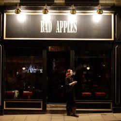 Photograph of a girl having a smoke outside a bar called Bad Apples.