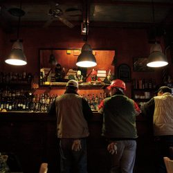 Photograph of two workmen wearing hard hats in a bar in Milan.