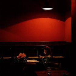 Photograph in a dark bar with red wall and a girl making a 'phone call.
