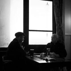 Black and white photograph of two people in a bar in Cromer Norfolk.