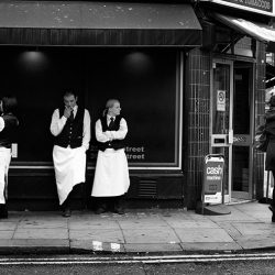 Black and white photograph of waiters in black wearing white aprons in Soho London.